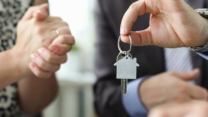 freepik-hand-realtor-hold-house-key-aganist-office